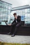 Επιχειρηματίας που χρησιμοποιεί το lap-top μιλώντας στο τηλέφωνο Στοκ εικόνες με δικαίωμα ελεύθερης χρήσης