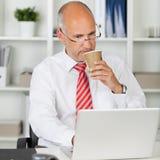 Επιχειρηματίας που χρησιμοποιεί το lap-top πίνοντας τον καφέ στο μίας χρήσης φλυτζάνι Στοκ Φωτογραφίες