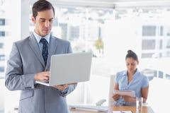 Επιχειρηματίας που χρησιμοποιεί το lap-top που στέκεται στην αρχή Στοκ εικόνα με δικαίωμα ελεύθερης χρήσης