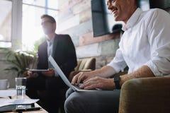 Επιχειρηματίας που χρησιμοποιεί το lap-top στη συνεδρίαση με τους εταιρικούς συναδέλφους Στοκ Εικόνες
