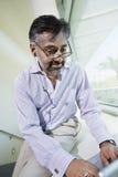 Επιχειρηματίας που χρησιμοποιεί το lap-top στο γραφείο Στοκ Εικόνες