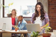 Επιχειρηματίας που χρησιμοποιεί το lap-top στο δημιουργικό γραφείο Στοκ Εικόνα