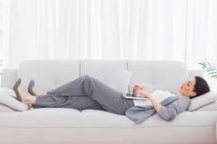 Επιχειρηματίας που χρησιμοποιεί το lap-top της που βρίσκεται στον καναπέ Στοκ Φωτογραφίες