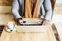 Επιχειρηματίας που χρησιμοποιεί το lap-top του στη καφετερία Στοκ Εικόνες