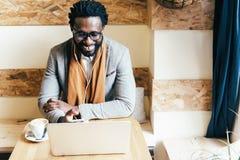 Επιχειρηματίας που χρησιμοποιεί το lap-top του στη καφετερία Στοκ εικόνα με δικαίωμα ελεύθερης χρήσης