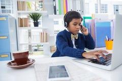 Επιχειρηματίας που χρησιμοποιεί το lap-top φορώντας το επικεφαλής σύνολο Στοκ Εικόνες