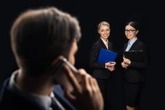 Επιχειρηματίας που χρησιμοποιεί το smartphone ενώ επιχειρηματίες που συνδέουν πίσω Στοκ εικόνες με δικαίωμα ελεύθερης χρήσης