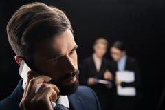 Επιχειρηματίας που χρησιμοποιεί το smartphone ενώ επιχειρηματίες που συνδέουν πίσω Στοκ Φωτογραφίες