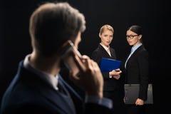 Επιχειρηματίας που χρησιμοποιεί το smartphone ενώ επιχειρηματίες που συνδέουν πίσω Στοκ φωτογραφία με δικαίωμα ελεύθερης χρήσης