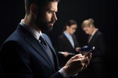 Επιχειρηματίας που χρησιμοποιεί το smartphone ενώ επιχειρηματίες που συνδέουν πίσω Στοκ Εικόνες
