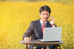Επιχειρηματίας που χρησιμοποιεί το smartphone και το lap-top στον τομέα λουλουδιών Στοκ εικόνα με δικαίωμα ελεύθερης χρήσης