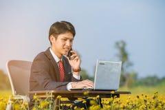 Επιχειρηματίας που χρησιμοποιεί το smartphone και το lap-top στον τομέα λουλουδιών Στοκ Φωτογραφίες
