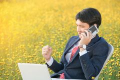 Επιχειρηματίας που χρησιμοποιεί το smartphone και το lap-top στον τομέα λουλουδιών Στοκ Εικόνες