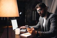 Επιχειρηματίας που χρησιμοποιεί το smartphone και το lap-top το στούντιο Νέο γενειοφόρο άτομο που εργάζεται για το νέο ξεκίνημα τ Στοκ Εικόνες