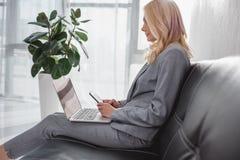 Επιχειρηματίας που χρησιμοποιεί το smartphone και το lap-top Στοκ Εικόνες