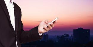 Επιχειρηματίας που χρησιμοποιεί το smartphone με την πόλη defocus στην αυγή Στοκ Εικόνες
