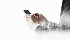 Επιχειρηματίας που χρησιμοποιεί το smartphone με τη διπλή πόλη έκθεσης, έννοιες τεχνολογίας επιχειρησιακών επικοινωνιών, που απομ Στοκ εικόνες με δικαίωμα ελεύθερης χρήσης