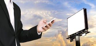 Επιχειρηματίας που χρησιμοποιεί το smartphone με τον κενό πίνακα διαφημίσεων για το διάστημα αντιγράφων στον όμορφο ουρανό Στοκ Εικόνες