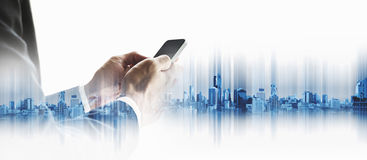 Επιχειρηματίας που χρησιμοποιεί το smartphone με το διπλό υπόβαθρο πόλεων έκθεσης, έννοια τεχνολογίας επιχειρησιακών επικοινωνιών Στοκ Εικόνα