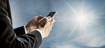 Επιχειρηματίας που χρησιμοποιεί το smartphone με το υπόβαθρο μπλε ουρανού και ηλιοφάνειας Στοκ Εικόνες