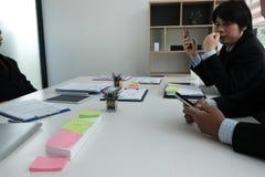 Επιχειρηματίας που χρησιμοποιεί το smartphone στην αίθουσα συνεδριάσεων εκμετάλλευση ατόμων κινητή Στοκ Εικόνες