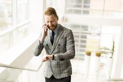 Επιχειρηματίας που χρησιμοποιεί το smartphone στο γραφείο Στοκ Εικόνα