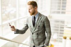 Επιχειρηματίας που χρησιμοποιεί το smartphone στο γραφείο Στοκ Εικόνες