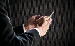 Επιχειρηματίας που χρησιμοποιεί το smartphone, στο θολωμένο καθαρό υπόβαθρο μετάλλων defocus μαύρο Στοκ Εικόνες
