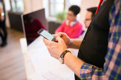 Επιχειρηματίας που χρησιμοποιεί το smartphone στο σύγχρονο γραφείο, κινηματογράφηση σε πρώτο πλάνο Στοκ Εικόνες