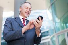 Επιχειρηματίας που χρησιμοποιεί το smartphone του Στοκ Εικόνες