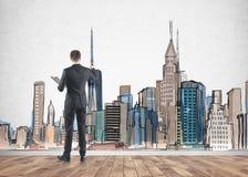 Επιχειρηματίας που χρωματίζει μια εικονική παράσταση πόλης στοκ εικόνες