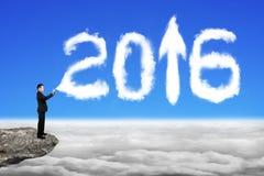 Επιχειρηματίας που ψεκάζει την άσπρη μορφή σύννεφων έτους του 2016 στο cloudsca ουρανού Στοκ Φωτογραφίες