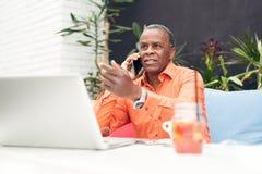 Επιχειρηματίας σε έναν καφέ, που μιλά σε κινητό Στοκ εικόνα με δικαίωμα ελεύθερης χρήσης