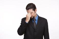 Επιχειρηματίας σε ένα μαύρο κοστούμι με την τσιμπώντας κορυφή πονοκέφαλου του αριθ. του Στοκ Φωτογραφίες