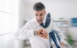 Επιχειρηματίας σε μια βιασύνη που ελέγχει το χρόνο στοκ φωτογραφία