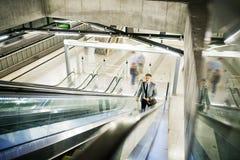 Επιχειρηματίας σε μια κυλιόμενη σκάλα σε έναν σταθμό μετρό Στοκ Εικόνες