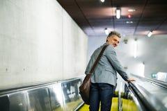 Επιχειρηματίας σε μια κυλιόμενη σκάλα σε έναν σταθμό μετρό Στοκ Εικόνα