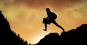 Επιχειρηματίας σκιαγραφιών που πηδά στο βουνό ενάντια στον ουρανό Στοκ φωτογραφίες με δικαίωμα ελεύθερης χρήσης