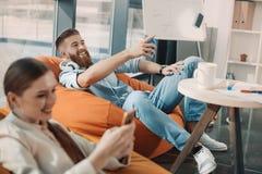Επιχειρηματίας στα ακουστικά που δείχνει μακριά ενώ επιχειρηματίας που χρησιμοποιεί το smartphone Στοκ Φωτογραφίες