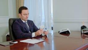 Επιχειρηματίας στα μετρώντας χρήματα τραπεζογραμματίων κοστουμιών απόθεμα βίντεο