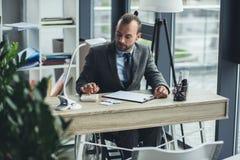Επιχειρηματίας στην αναπηρική καρέκλα συνεδρίαση στον εργασιακό χώρο και εργασία με τα έγγραφα στην αρχή Στοκ Φωτογραφίες