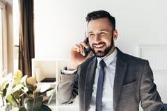 Επιχειρηματίας στην επίσημη ένδυση που μιλά στο smartphone στο γραφείο Στοκ Εικόνες