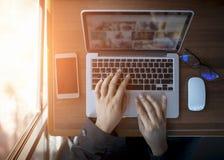 Επιχειρηματίας στην εργασία Τοπ άποψη κινηματογραφήσεων σε πρώτο πλάνο του ατόμου που εργάζεται στο lap-top καθμένος στο ξύλινο γ στοκ φωτογραφίες