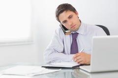 Επιχειρηματίας στην κλήση γράφοντας στο ημερολόγιο στο γραφείο Στοκ Εικόνα