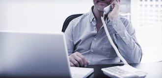 Επιχειρηματίας στην κλήση μπροστά από το lap-top στο γραφείο γραφείων Στοκ εικόνα με δικαίωμα ελεύθερης χρήσης
