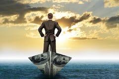 Επιχειρηματίας στη βάρκα δολαρίων Στοκ Εικόνες