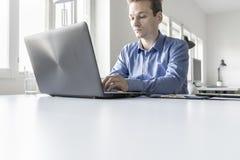 Επιχειρηματίας στις πληροφορίες δακτυλογράφησης γραφείων για το φορητό προσωπικό υπολογιστή Στοκ εικόνες με δικαίωμα ελεύθερης χρήσης