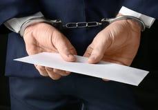Επιχειρηματίας στις χειροπέδες που κρατά το φάκελο με τη δωροδοκία, Στοκ Φωτογραφίες