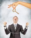 Επιχειρηματίας στις χειροπέδες και το μεγάλο χέρι που προσφέρουν το κλειδί Στοκ εικόνες με δικαίωμα ελεύθερης χρήσης