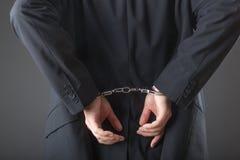 Επιχειρηματίας στις χειροπέδες που συλλαμβάνεται και που απομονώνεται Στοκ Εικόνες